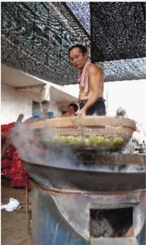 一工人正把未成熟的青枣放入开水里加工。
